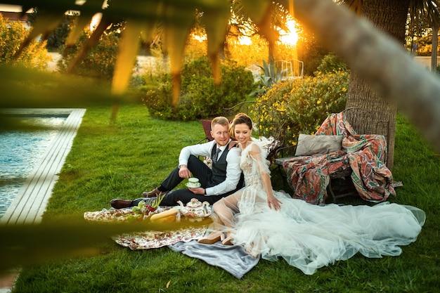 Recém-casados sentam e bebem chá no jardim ao pôr do sol.