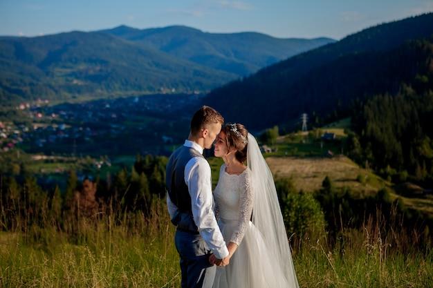 Recém-casados sorriem e se abraçam entre a campina no topo da montanha