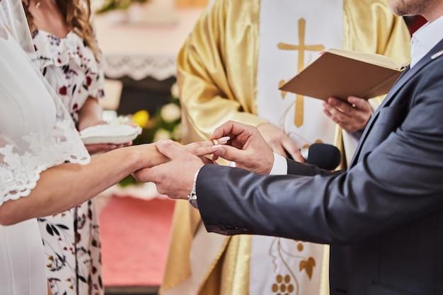 Recém-casados trocam alianças durante um casamento em uma igreja católica