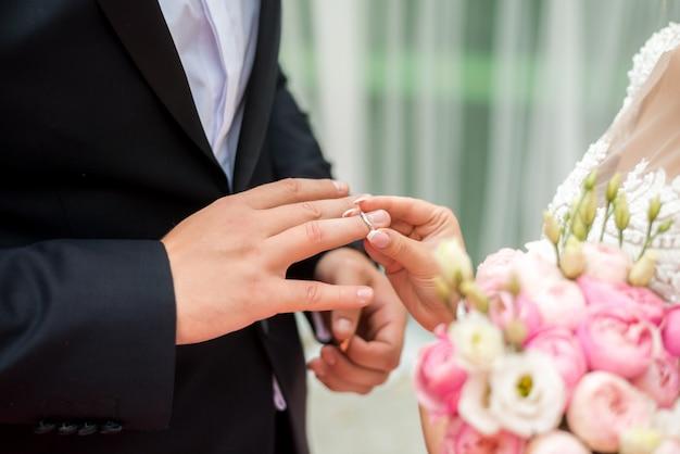 Recém-casados trocam alianças, noivo coloca o anel na mão da noiva no cartório de casamento.