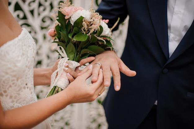 Recém-casados trocando alianças, noiva colocando o anel na mão do noivo