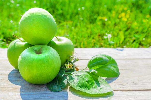 Recém colhidas maçãs verdes na mesa de madeira sobre a grama verde