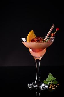 Recém-feitos coquetéis margarita em copos com hortelã e laranja em preto.