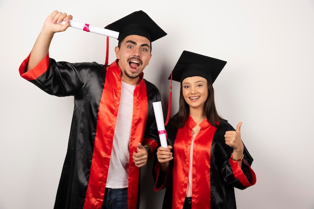 Recém-formados com diploma fazendo polegares para cima em branco.