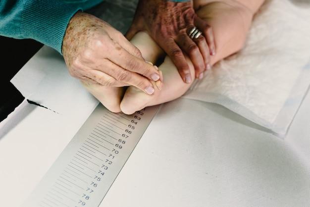 Recém nascida na clínica do pediatra medindo altura e altura do bebê com a ajuda de uma régua.