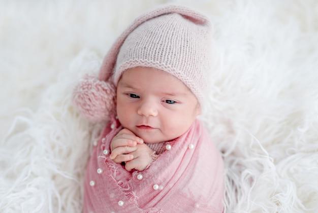 Recém-nascido acordado bonito no chapéu de malha