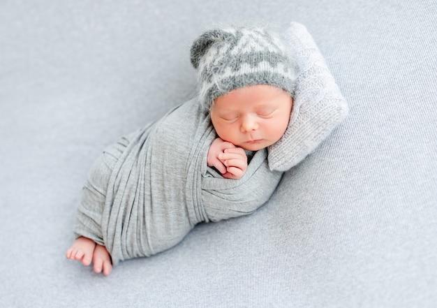 Recém-nascido bonito dormindo no travesseiro minúsculo