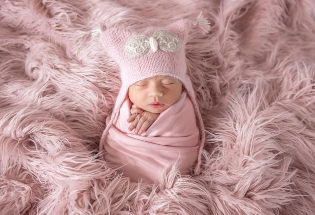 Recém-nascido com chapéu de gorro em um tapete felpudo