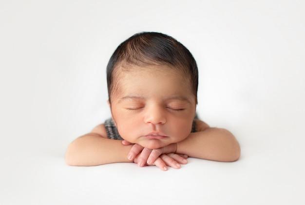 Recém-nascido deitado pacificamente pequeno menino bonito e simpático