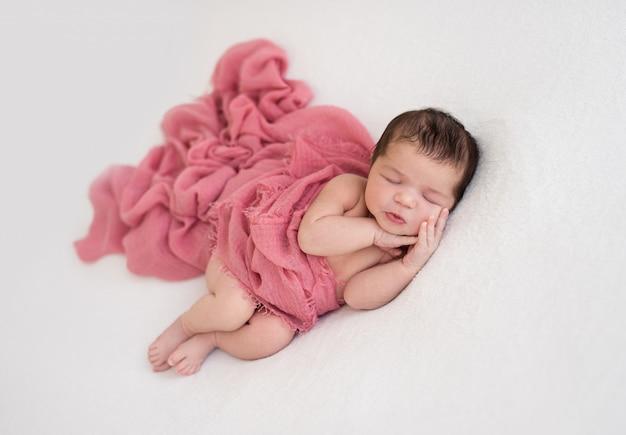Recém-nascido dormindo bonito deitado de lado