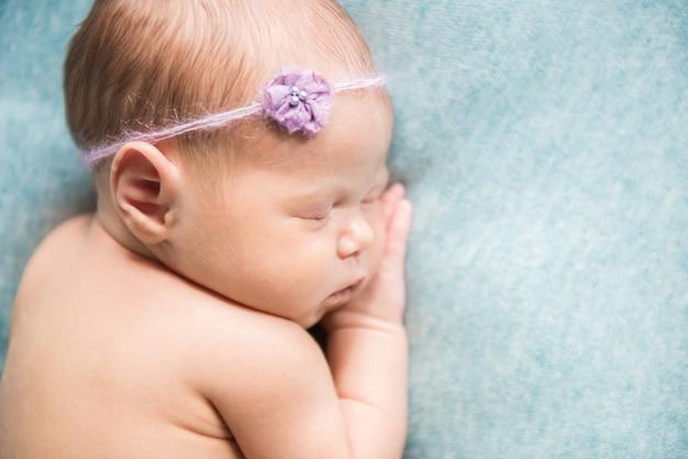 Recém-nascido dormindo com a mão embaixo da bochecha