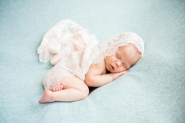 Recém-nascido dormindo com a mão embaixo da bochecha Foto Premium