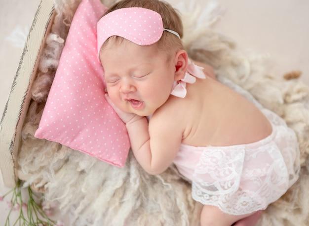 Recém-nascido dormindo na cama pequena