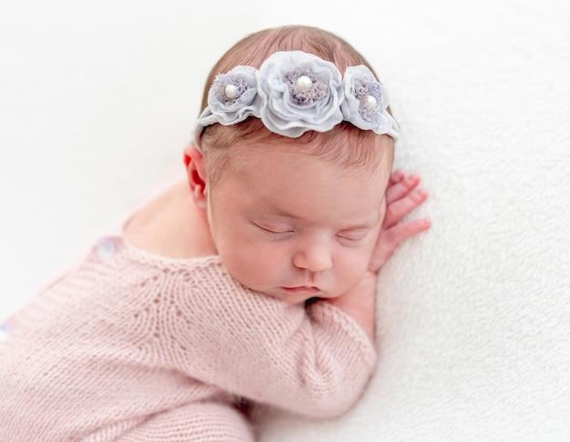 Recém-nascido fofo em terno de malha rosa dormindo na barriga