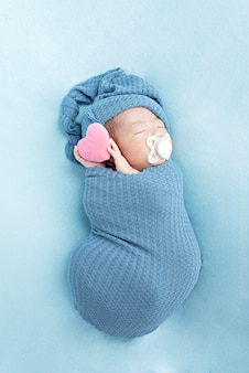 Recém-nascido menina dormindo e segurando coração. criança pequena, soneca do dia na cama dos pais
