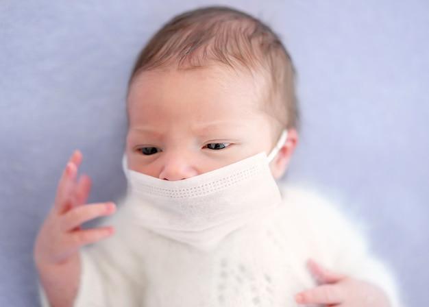 Recém-nascido vestindo máscara médica