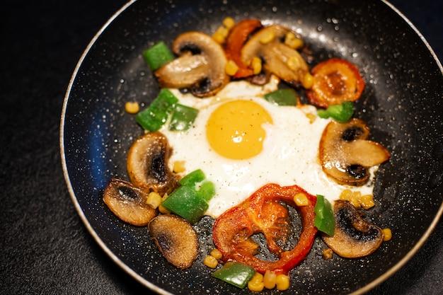 Recém ovos fritos com legumes em uma panela