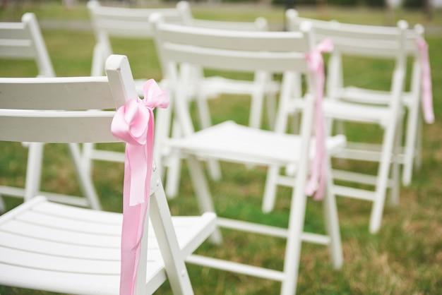Recentemente corte a bela guirlanda de flores de casamento vermelho e roxo na cadeira.
