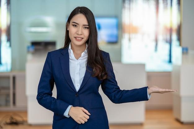 Recepção asiática que dá boas-vindas ao cliente no balcão da sala de exposições do carro para o cliente do serviço