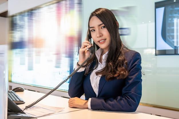 Recepção asiática recebendo a chamada no balcão da sala de exposições para atender o cliente por telefone