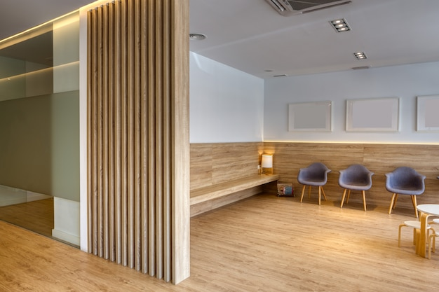 Recepção de design moderno com cadeiras cinza, quadros, paredes brancas. piso e tela de madeira. clinica odontológica.