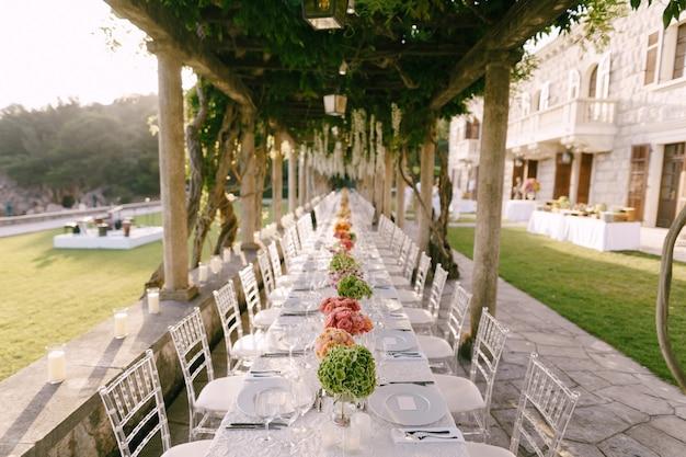 Recepção de mesa de jantar de casamento uma mesa muito longa para convidados com uma toalha de mesa branca floral