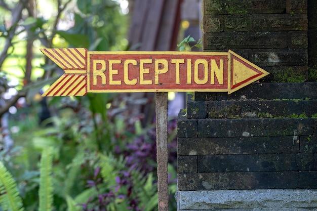 Recepção de texto em uma placa de madeira perto de um hotel tropical na ilha de bali, na indonésia. inscrição de placa de recepção de madeira nos trópicos asiáticos, close-up