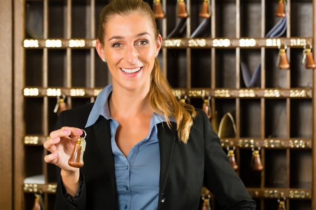 Recepção do hotel, mulher segurando a chave na mão