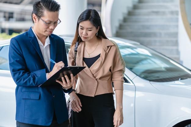 Recepcionista asiática verificando a lista de manter ao cliente no centro de serviço de manutenção