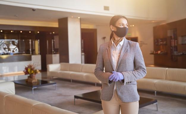 Recepcionista calma e elegante usando máscara de tecido e luvas de borracha durante o trabalho