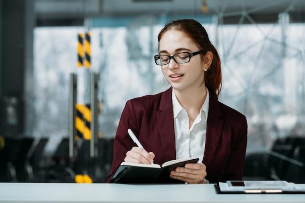 Recepcionista de empresa amigável. espaço de trabalho do office. mulher jovem ruiva fazendo anotações no planejador de dia útil.