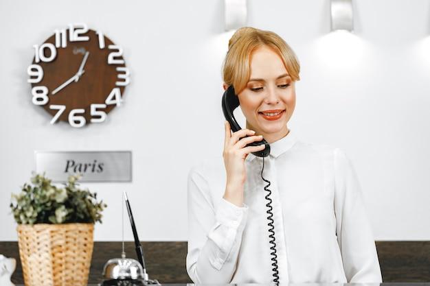 Recepcionista de hotel bonita e simpática falando ao telefone de perto