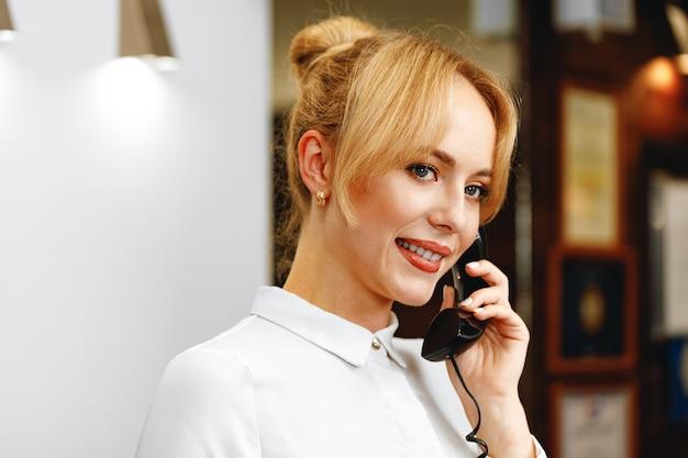 Recepcionista de hotel bonita e simpática falando ao telefone