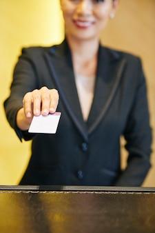 Recepcionista de hotel feminina positiva dando a chave eletrônica do quarto para o hóspede do hotel, foco seletivo
