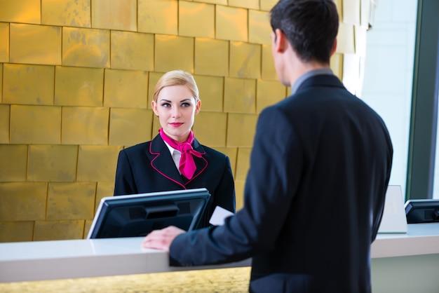 Recepcionista de hotel verificar no homem dando cartão-chave
