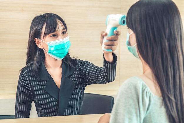 Recepcionista e hóspede usando máscara facial na recepção.