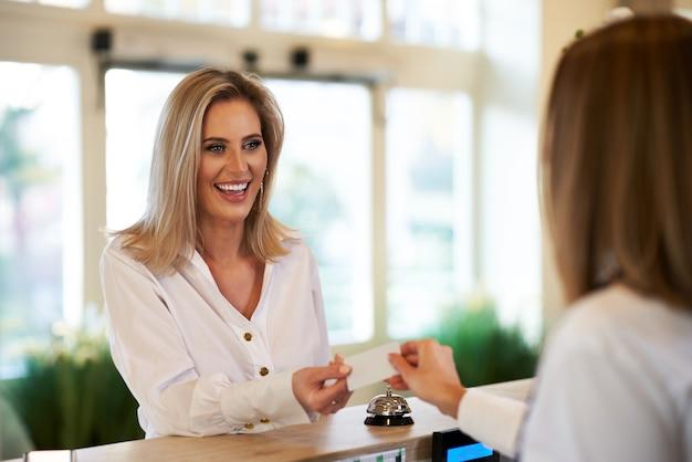 Recepcionista entregando cartão-chave para empresária na recepção do hotel