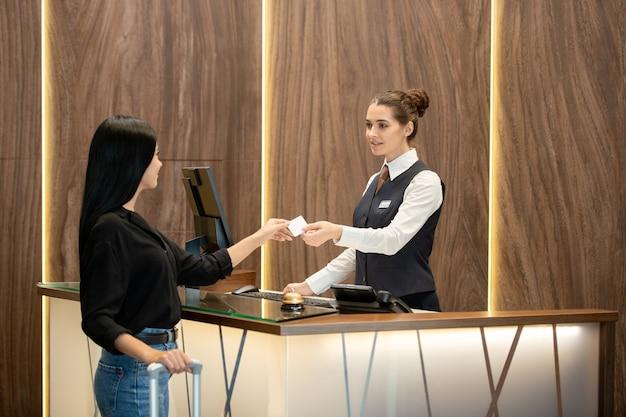 Recepcionista jovem morena de uniforme em pé no local de trabalho e passando o cartão plástico para um dos hóspedes no balcão da recepção no saguão do hotel