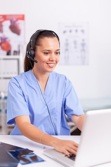 Recepcionista médica usando fone de ouvido com microfone em hospital privado, digitando no laptop médico de saúde sentado na mesa usando o computador na clínica moderna, olhando para o monitor.