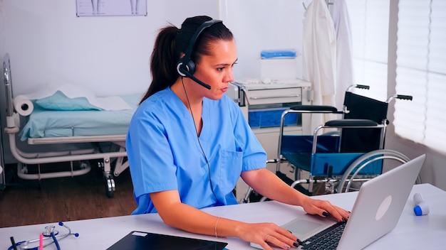 Recepcionista, operadora falando online com pacientes usando fone de ouvido, ajudando pessoas com problemas de saúde sentadas no local de trabalho do hospital. médico de saúde, assistente durante comunicação de telessaúde