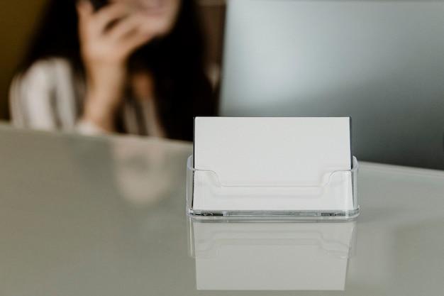 Recepcionista sentada ao lado do cartão da empresa
