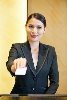 Recepcionista sorridente de hotel ou centro de negócios oferecendo cartão eletrônico