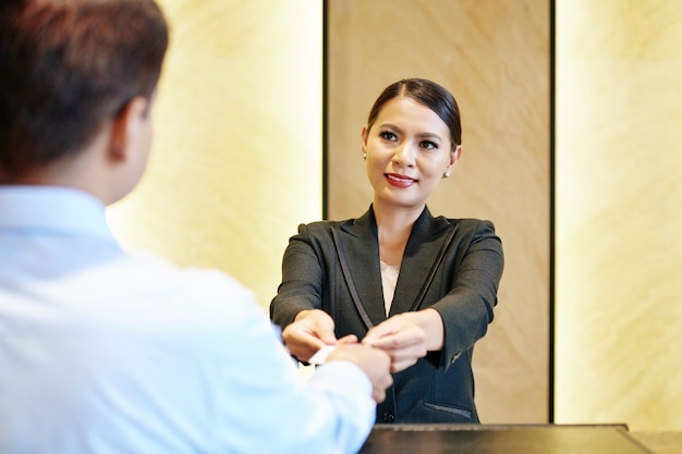Recepcionista sorridente entregando cartão eletrônico ao hóspede do hotel com as duas mãos
