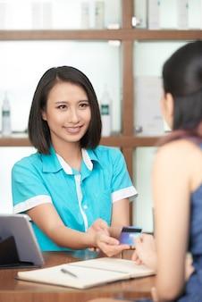 Recepcionista sorridente, tendo o pagamento do cliente