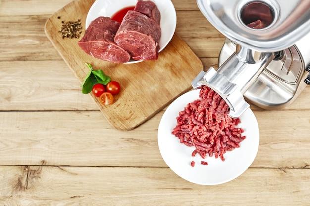 Recheio de carne fresco, tábua de cortar com moedor de carne na mesa da cozinha. vista do topo. copie o espaço.