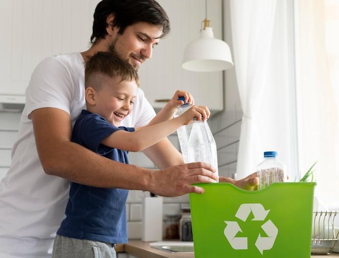 Reciclagem de homem e criança de tiro médio