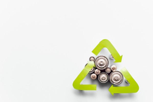 Reciclagem de lixo, descarte de lixo, conceito de meio ambiente e ecologia - close up de pilhas alcalinas usadas e símbolo de reciclagem verde