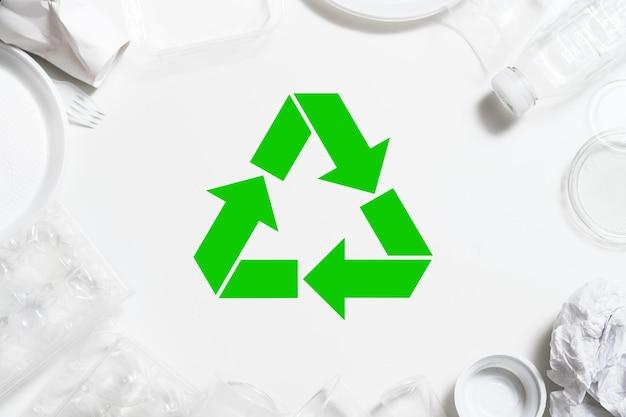 Reciclagem de lixo. proteção ambiental. talheres de plástico dispostos em torno do símbolo verde.