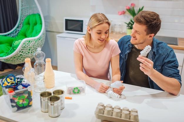 Reciclagem, reutilização. família jovem sorridente, classificando as lâmpadas brancas em um pequeno recipiente com símbolo de reciclagem enquanto está sentado na cozinha