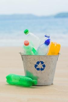 Reciclar, cesta com garrafa de plástico na praia